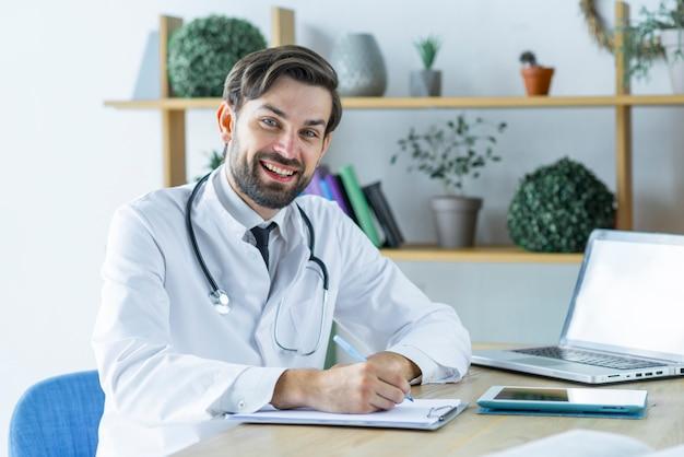 Jovem médico alegre fazendo anotações Foto gratuita