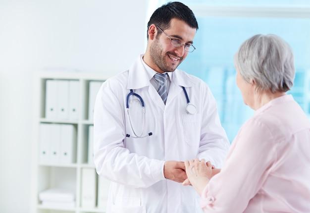 Jovem médico apoiando o seu paciente Foto gratuita