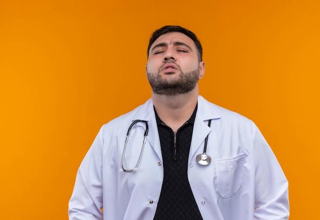 Jovem médico barbudo preocupado com jaleco branco e estetoscópio parecendo cansado e estressado fechando os olhos Foto gratuita