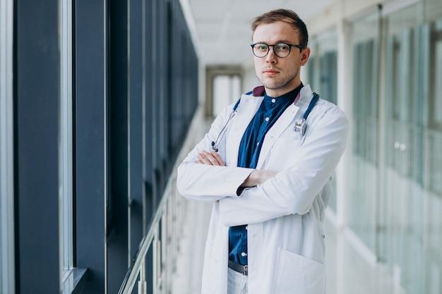 Jovem médico bonitão com estetoscópio na clínica Foto gratuita