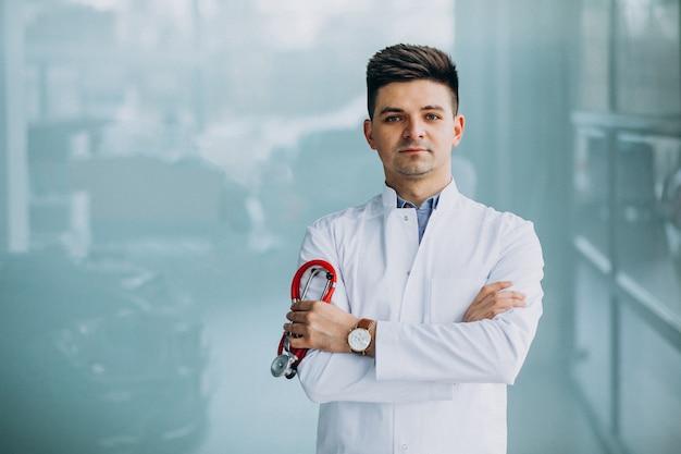 Jovem médico bonito em uma túnica médica com estetoscópio Foto gratuita