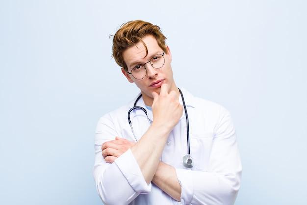 Jovem médico chefe vermelho olhando sério, confuso, incerto e pensativo Foto Premium