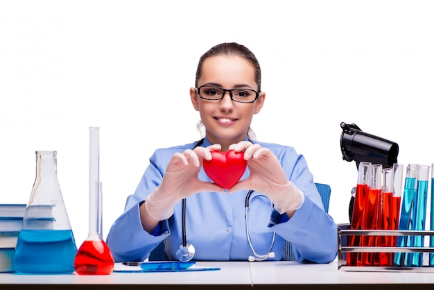 Jovem médico com coração vermelho isolado no branco Foto Premium