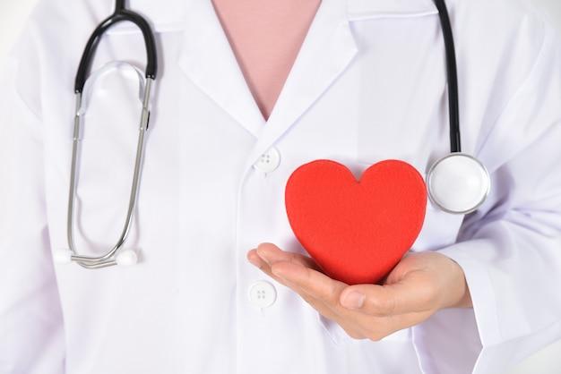 Jovem médico feminino com estetoscópio segurando coração vermelho na mão dela. Foto Premium
