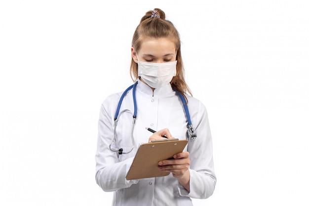 Jovem médico feminino em traje médico branco com estetoscópio em máscara protetora branca, anotando notas em branco Foto gratuita