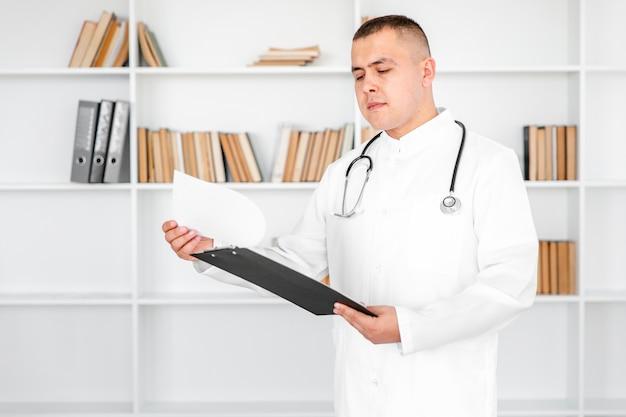 Jovem médico olhando nas folhas de uma prancheta Foto gratuita