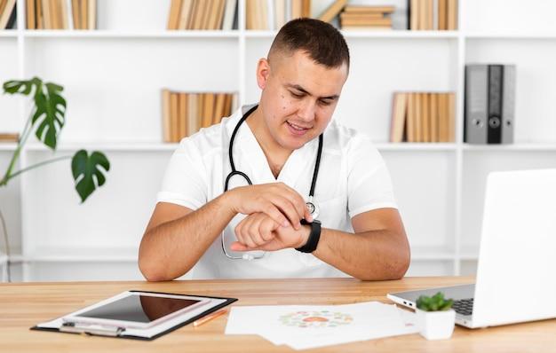 Jovem médico olhando para o relógio Foto gratuita