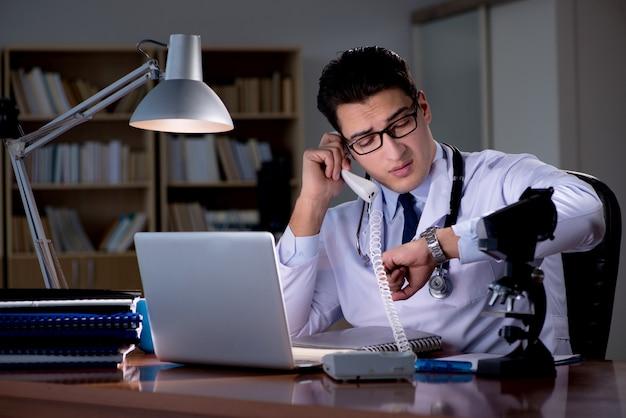 Jovem médico trabalhando até tarde no escritório Foto Premium