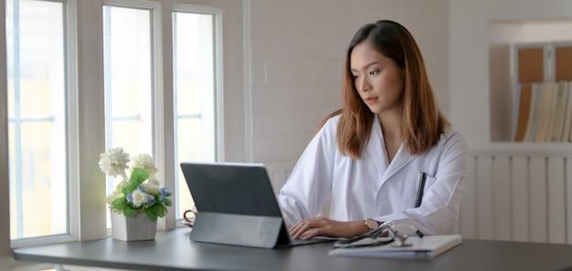 Jovem médico trabalhando em registros médicos com tablet no escritório do hospital Foto Premium