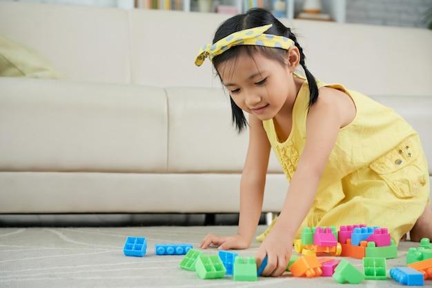 Jovem menina asiática ajoelhada no chão em casa e brincando com blocos de construção coloridos Foto gratuita