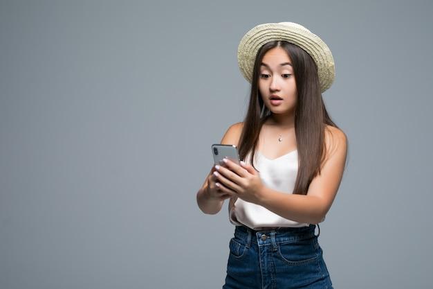 Jovem menina asiática com chapéu de palha usar telefone em fundo cinza Foto gratuita