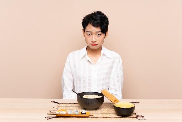 Jovem menina asiática em uma mesa com tigela de macarrão e sushi triste Foto Premium