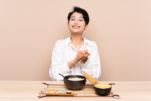 Jovem menina asiática em uma mesa com uma tigela de macarrão e sushi aplaudindo Foto Premium