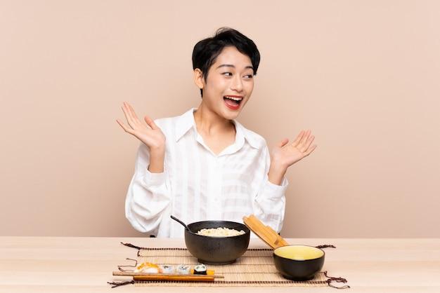 Jovem menina asiática em uma mesa com uma tigela de macarrão e sushi com expressão facial de surpresa Foto Premium