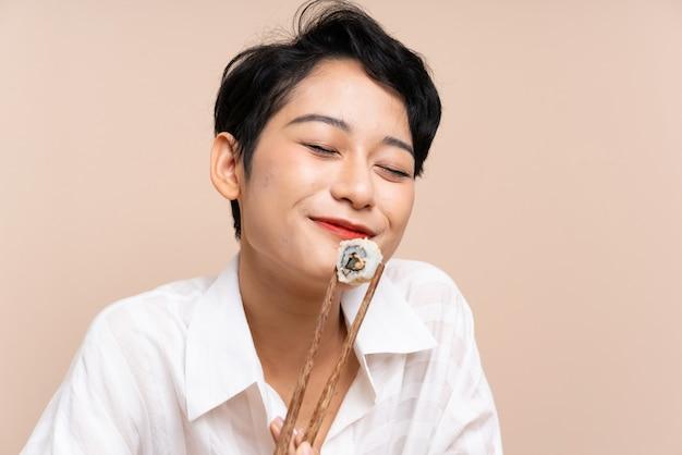 Jovem menina asiática em uma mesa com uma tigela de macarrão e sushi Foto Premium