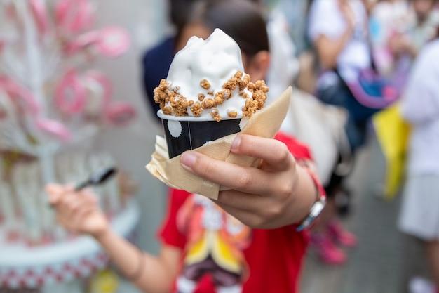 Jovem menina asiática feliz desfrutando de seu creme macio, sorvete japonês, com cobertura de granola Foto Premium