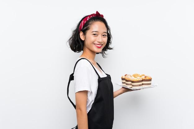 Jovem, menina asiática, segurando, lotes bolo muffin, sorrindo muito Foto Premium