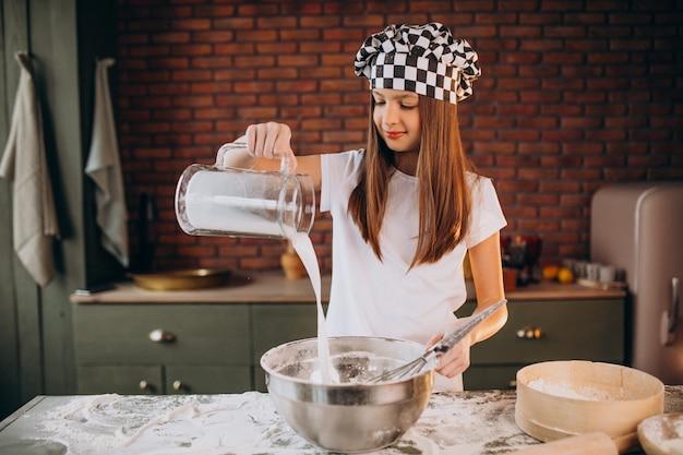 Jovem menina assando bolos na cozinha no café da manhã Foto gratuita