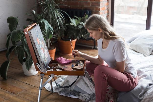 Jovem menina bonita com pincel e paleta sentado perto de imagem de desenho de cavalete Foto Premium