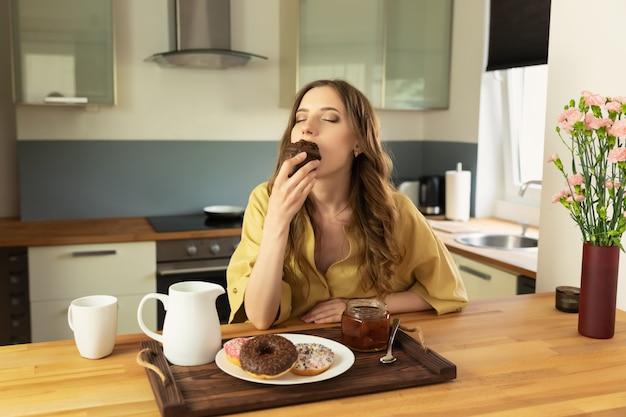Jovem menina bonita está tomando café da manhã em casa na cozinha. ela bebe o café da manhã e come um bolinho de chocolate. Foto Premium