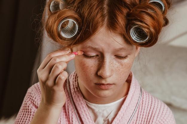 Jovem menina bonita maquiagem na cama no quarto. ruivo e calafetando com rolinhos na cabeça em um roupão de banho. Foto Premium