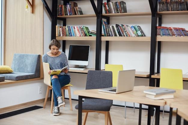 Jovem menina de cabelos claros inteligente com penteado bob em roupas casuais, sentado na cadeira na biblioteca moderna, lendo o livro favorito, relaxando após um longo dia de estudo Foto gratuita