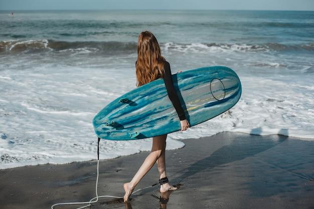 Jovem menina linda posando na praia com uma prancha de surf, mulher surfista, ondas do mar Foto gratuita