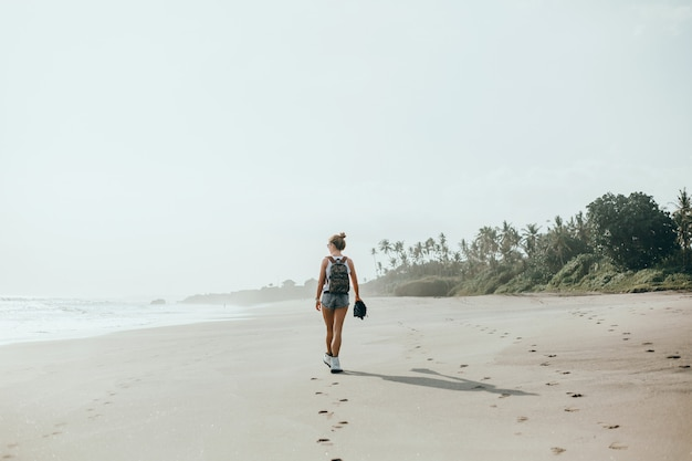 Jovem menina linda posando na praia, oceano, ondas, sol brilhante e pele bronzeada Foto gratuita
