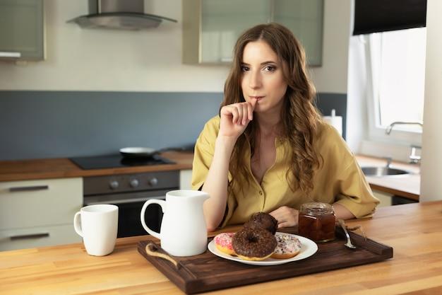 Jovem menina linda tomando café da manhã em casa na cozinha. a garota come alimentos não saudáveis e de alta caloria. Foto Premium
