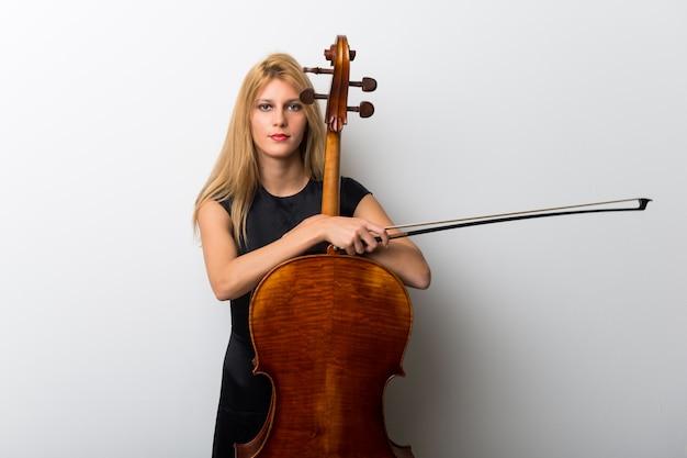 Jovem menina loira com seu violoncelo posando na parede branca Foto Premium