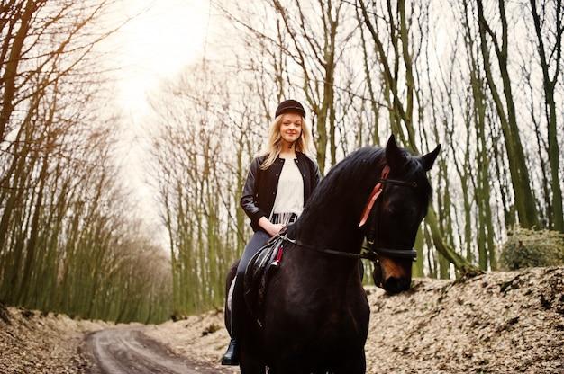 Jovem menina loira elegante, andar a cavalo na floresta de outono Foto Premium