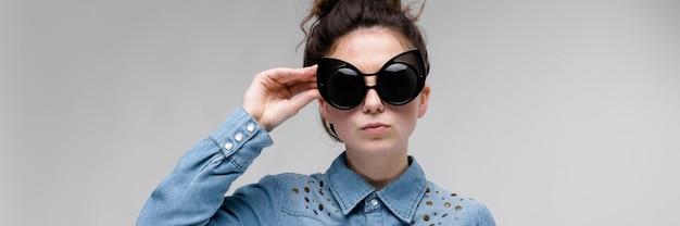 Jovem menina morena de óculos escuros. óculos de gato. o cabelo está reunido em um coque. a menina ajusta a camisa e os óculos. Foto Premium
