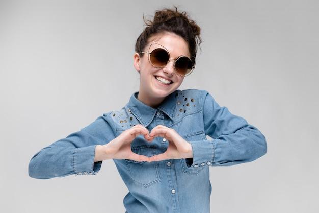 Jovem menina morena de óculos escuros. óculos de gato. o cabelo está reunido em um coque. a menina mostra as mãos do coração. Foto Premium