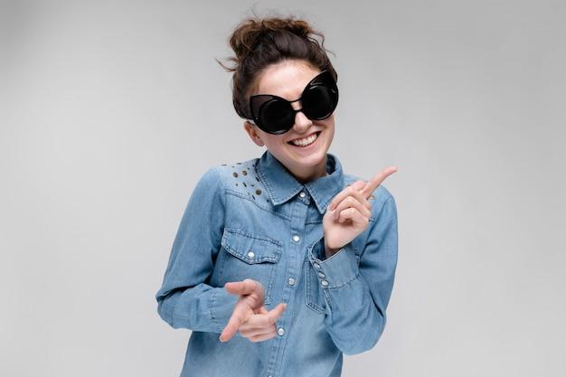 Jovem menina morena de óculos escuros. óculos de gato. o cabelo está reunido em um coque. garota dançando. Foto Premium