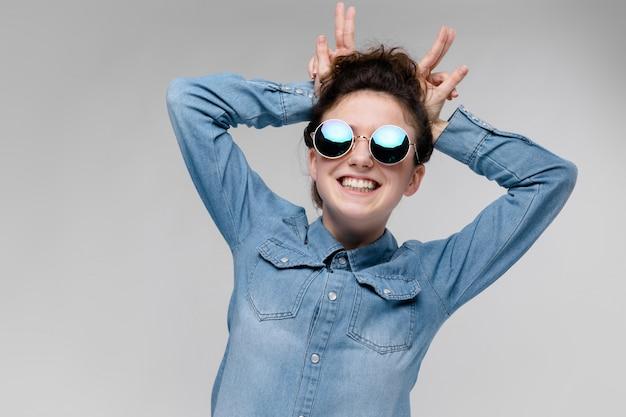 Jovem menina morena de óculos redondos. os cabelos são reunidos em um coque. a garota fez um chifre. Foto Premium