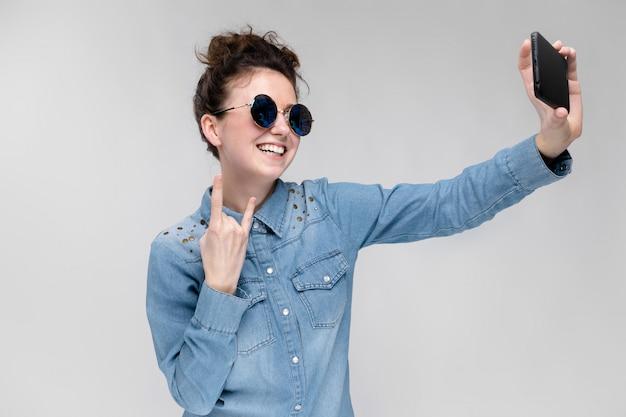 Jovem menina morena de óculos redondos. os cabelos são reunidos em um coque. menina com um telefone preto. a garota faz selfie. Foto Premium