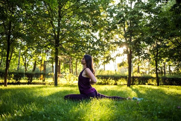 Jovem menina morena fazendo yoga em uma esteira no parque ao pôr do sol Foto Premium
