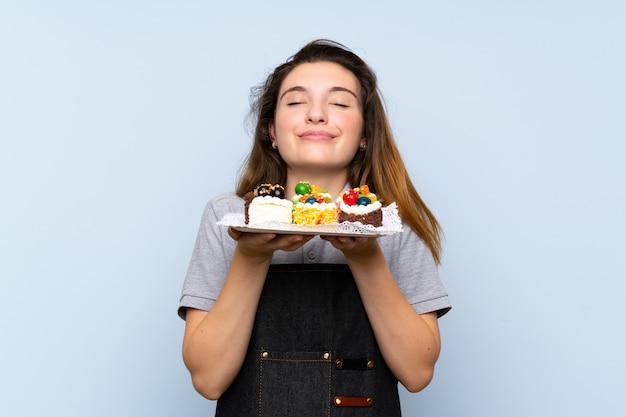 Jovem menina morena segurando mini bolos, apreciando o cheiro deles Foto Premium