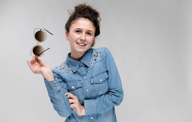 Jovem menina morena segurando óculos na mão. óculos de gato. o cabelo está reunido em um coque. Foto Premium