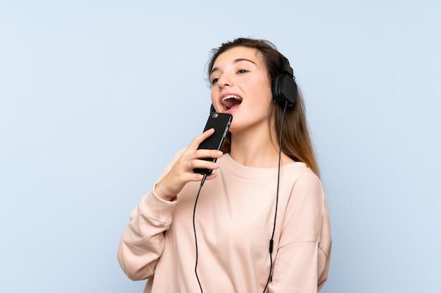 Jovem menina morena usando o celular com fones de ouvido e cantando Foto Premium
