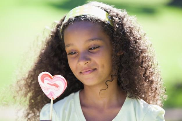 Jovem, menina, segurando, coração, lollipop, parque Foto Premium