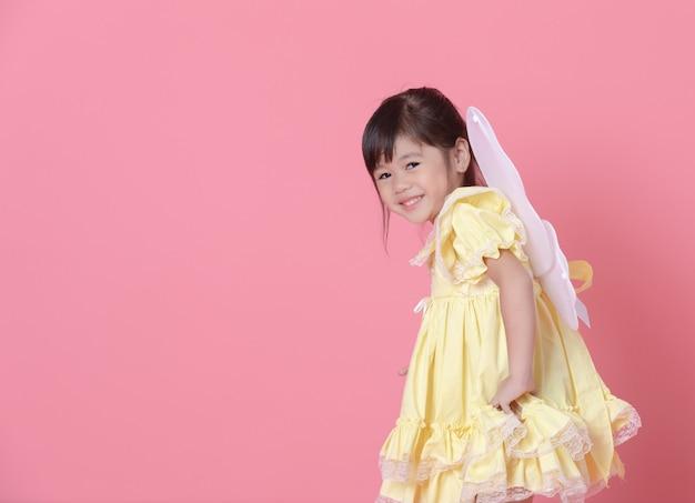 Jovem menina vestir-se como um anjo e brincar com as asas. Foto Premium