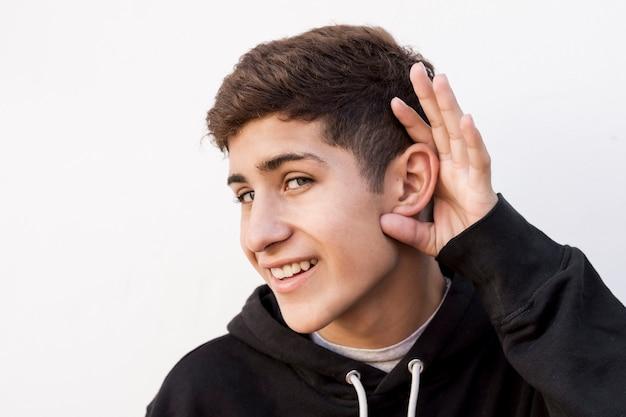 Jovem, menino adolescente, tentando, escutar, algo, contra, branca, fundo Foto gratuita