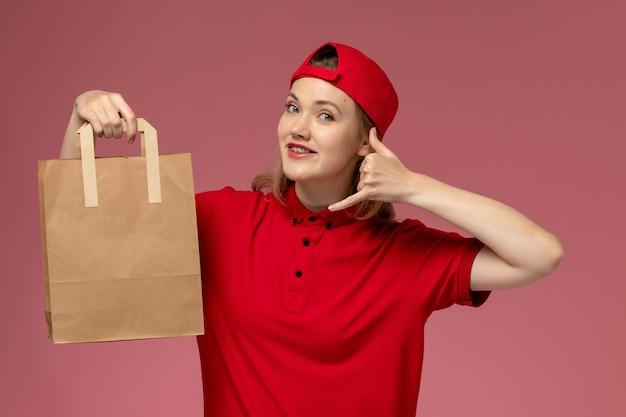 Jovem mensageira de frente com uniforme vermelho e capa segurando um pacote de comida para entrega, sorrindo na parede rosa Foto gratuita