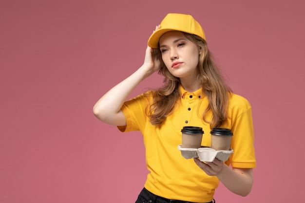 Jovem mensageira de frente, de uniforme amarelo, segurando xícaras de café de plástico e pensando no fundo rosa escuro. Foto gratuita