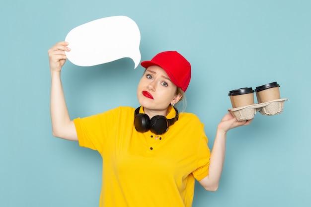 Jovem mensageira de frente para mulher de camisa amarela e capa vermelha segurando xícaras de café cartaz branco sobre o trabalho do espaço azul Foto gratuita
