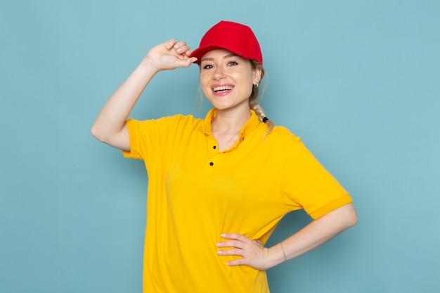 Jovem mensageira de frente para mulher de camisa amarela e capa vermelha, sorrindo e posando para a garota de trabalho do espaço azul Foto gratuita