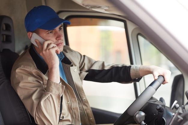 Jovem mensageiro de uniforme relatando sobre a entrega feita pelo celular enquanto dirigia a van Foto Premium