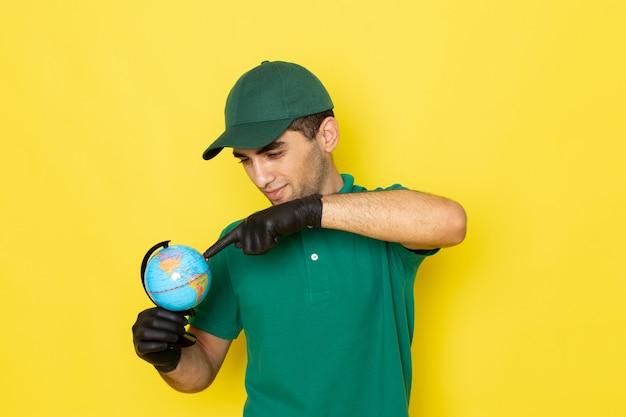 Jovem mensageiro masculino com boné verde e camisa verde segurando o globo terrestre com luvas pretas amarelas Foto gratuita