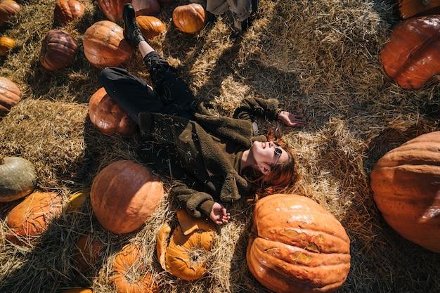 Jovem mentira em palheiros entre abóboras. vista de cima Foto gratuita